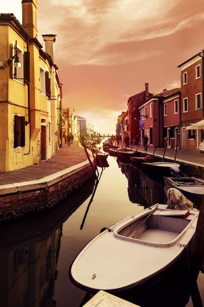 Beau coucher de soleil avec bateaux, bâtiments et eau. lumière du soleil. toning. burano, italie. Photo gratuit