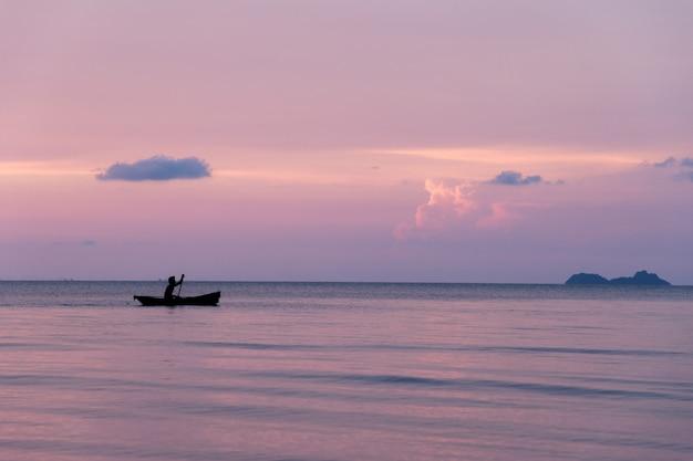 Beau coucher de soleil sur la plage et la silhouette du bateau, île de samui en thaïlande Photo Premium