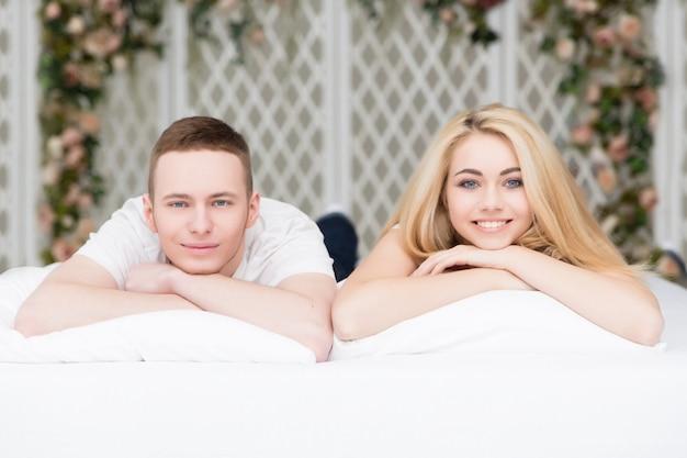 Beau couple amoureux allongé sur le lit Photo Premium