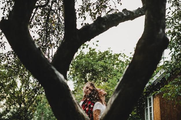 Le beau couple amoureux embrassant dans le parc sous la pluie Photo gratuit