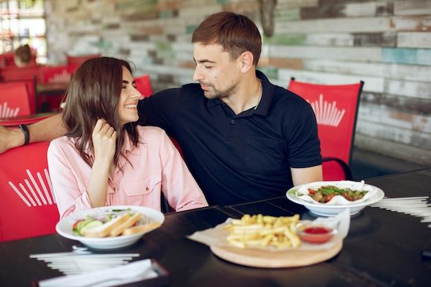 Beau couple assis dans un café d'été Photo gratuit