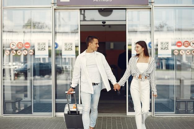 Beau couple debout près de l'aéroport Photo gratuit