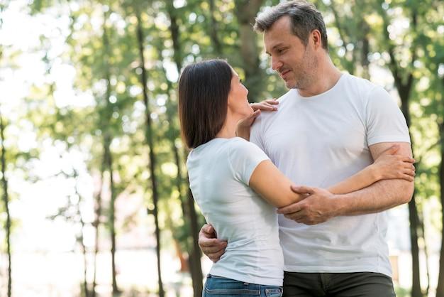 Beau Couple Embrassant Et Se Regardant Dans Le Parc Photo gratuit