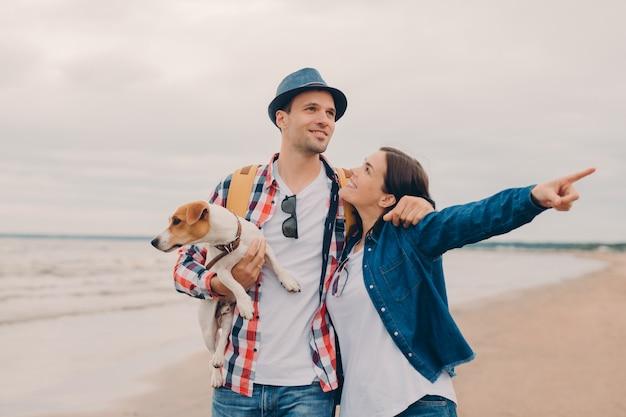 Beau couple embrasse et marche à l'extérieur sur la plage de sable fin, porte chien préféré Photo Premium