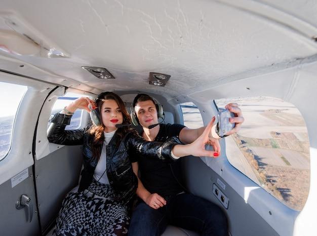 Beau Couple Fait Selfie à L'intérieur De L'hélicoptère Avec Un Paysage à Couper Le Souffle Par La Fenêtre Photo gratuit