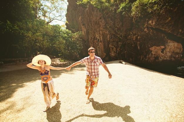 Beau couple heureux tenant par la main, marchant sur la plage avec les montagnes par une journée ensoleillée, à l'extérieur. une fille au chapeau et un gars en vacances dans un pays tropical. mode de vie voyage et tourisme, lune de miel Photo Premium