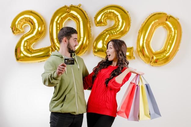 Beau couple homme et femme tenant carte de crédit et des sacs colorés devant des ballons de 2020 Photo Premium