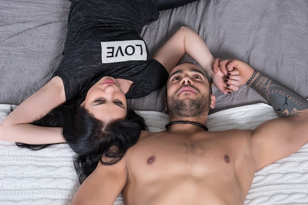 Beau Couple International D'homme à La Poitrine Nue Et Femme Brune Allongée Sur Le Lit Douillet Gris Dans La Chambre Photo Premium