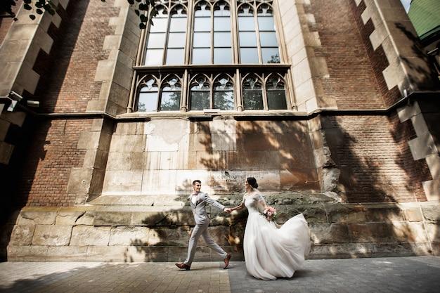 Beau couple de jeunes mariés à pied près de la vieille église chrétienne Photo Premium