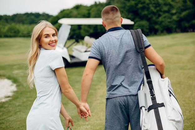 Beau couple jouant au golf sur un parcours de golf Photo gratuit