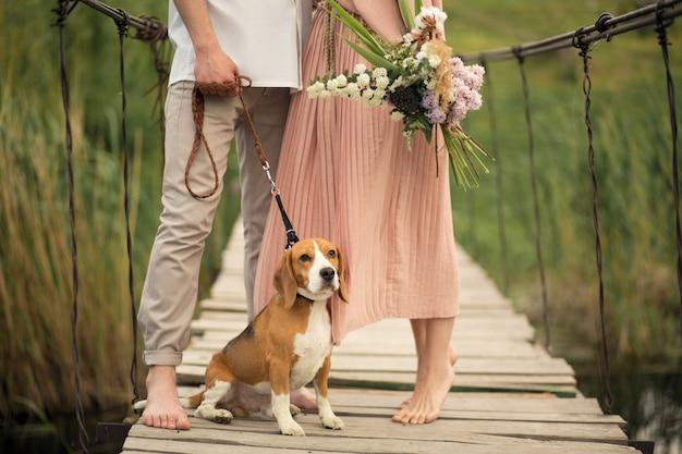 Beau couple marchant avec un chien sur le pont Photo Premium