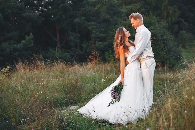 Beau couple de mariage dans un champ d'été Photo gratuit
