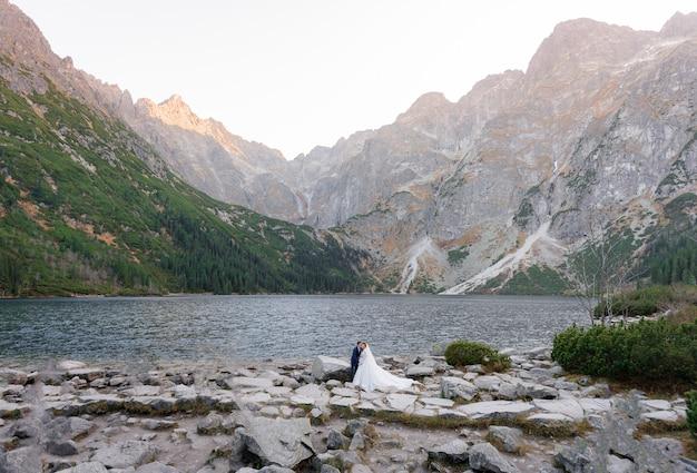 Beau Couple De Mariage Se Tient Devant Une Vue Pittoresque Sur Le Lac Dans Les Hautes Montagnes Photo gratuit