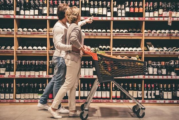 Beau Couple Parle Et Souriant Tout En Choisissant Du Vin. Photo Premium