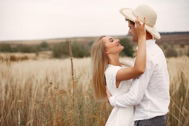 Beau couple passe du temps sur un champ d'automne Photo gratuit