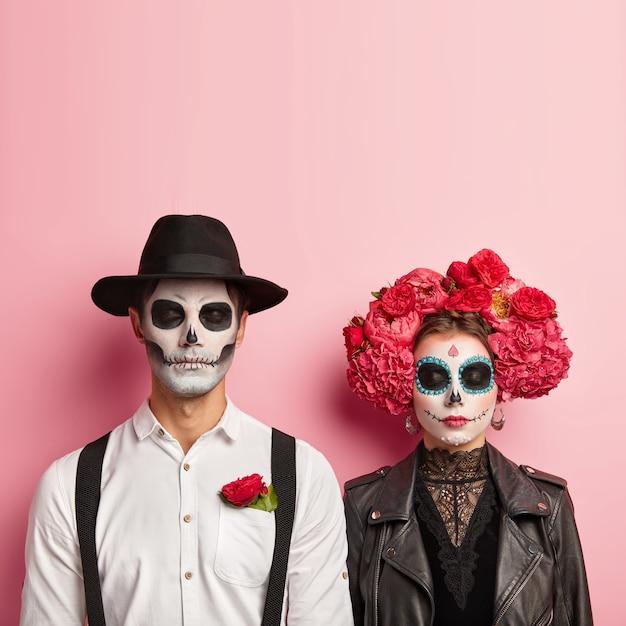 Beau Couple Porte Un Costume De Zombie Pour Halloween, Se Maquille Le Crâne, L'homme Porte Un Chapeau Et Une Chemise Blanche Avec Une Rose Rouge Dans La Poche, Une Femme En Veste De Cuir Noir Et Une Couronne De Fleurs, Attendez La Fête Ensemble Photo gratuit