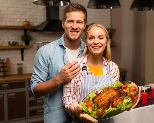 Beau couple en regardant la caméra et en tenant la dinde de thanksgiving Photo gratuit
