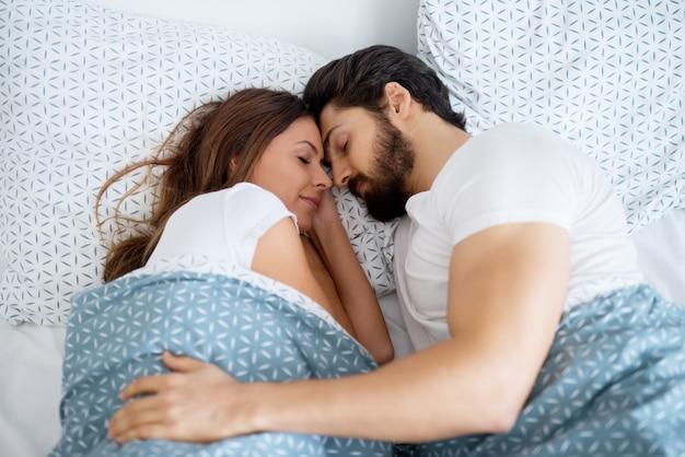 Beau Couple Romantique Amoureux Dormir Ensemble étreint Sur Le Lit à La Maison Ou à L'hôtel. Photo Premium