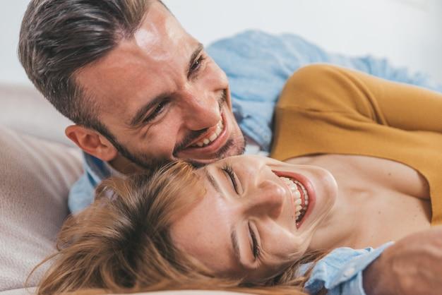 Beau Couple Romantique S'amuser à Rire Ensemble En Regardant La Télévision. Les Jeunes Amoureux à La Maison Passent Du Temps Ensemble. Photo Premium