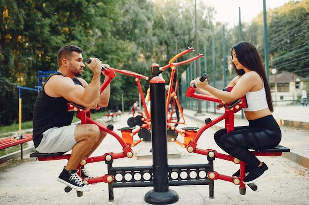 Beau couple s'entraînant dans un parc d'été Photo gratuit