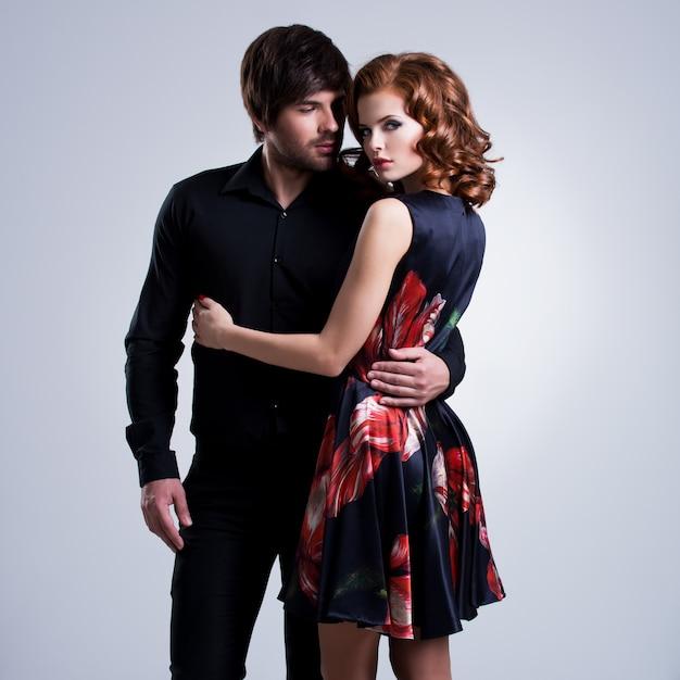 Beau Couple Sexy Amoureux Debout Sur Fond Gris Photo gratuit