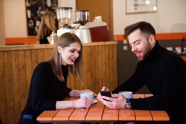 Beau, couple souriant, dans, café, utilisation, téléphone Photo Premium