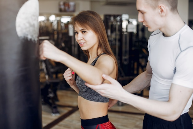 Un beau couple sportif est engagé dans une salle de sport Photo gratuit