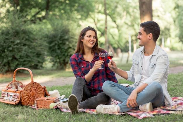 Beau couple tinter les verres à vin au pique-nique Photo gratuit