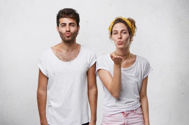 Beau Couple En Vêtements Décontractés Blancs Soufflant Baiser Montrant Leur Amour. Photo gratuit
