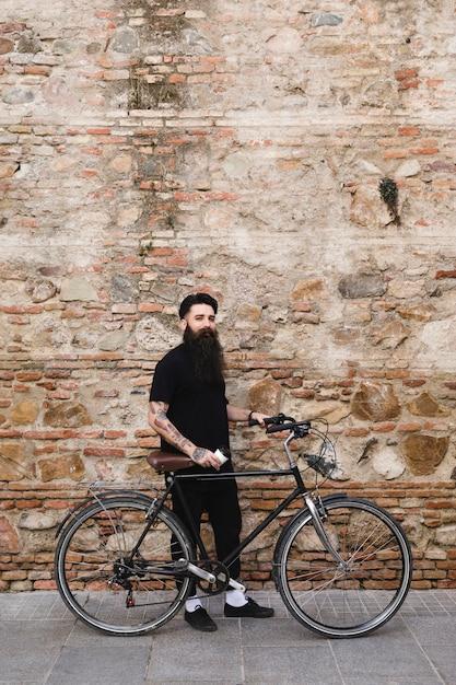 Beau cycliste debout avec vélo Photo gratuit