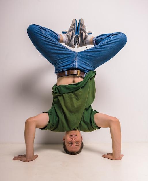 Beau danseur de pause debout sur sa tête et ses mains. Photo Premium