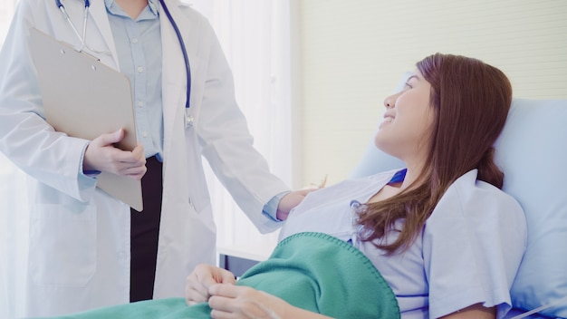 Beau docteur asiatique intelligent et patient discutant et expliquant quelque chose avec le presse-papier Photo gratuit