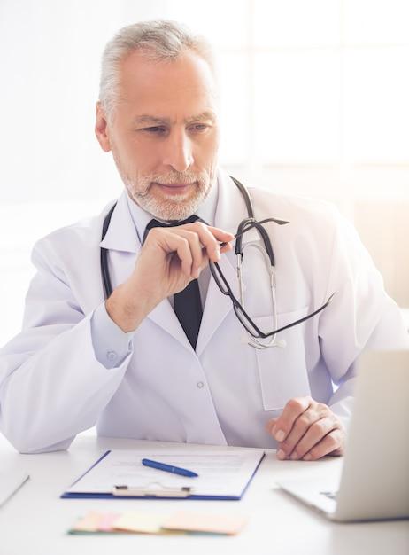 Beau docteur en blouse blanche utilise un ordinateur portable. Photo Premium