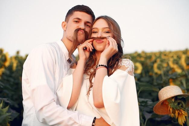 Beau et élégant couple dans un champ de tournesols Photo gratuit