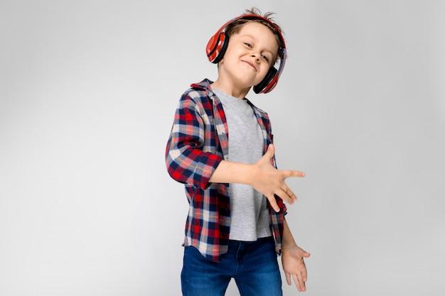 Un beau garçon dans une chemise à carreaux, une chemise grise et un jean se dresse sur gris Photo Premium