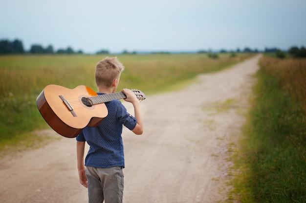 Beau garçon avec guitare, marchant sur la route en jour d'été. vue arrière Photo Premium