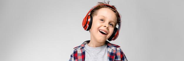 Un beau garçon vêtu d'une chemise à carreaux, d'une chemise grise et d'un jean. un garçon au casque rouge. le garçon tient ses mains sur son ventre. le garçon rit. Photo Premium