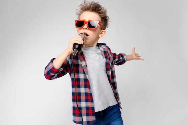 Un beau garçon vêtu d'une chemise à carreaux, d'une chemise grise et d'un jean. un garçon portant des lunettes de soleil. garçon roux chante dans le micro Photo Premium