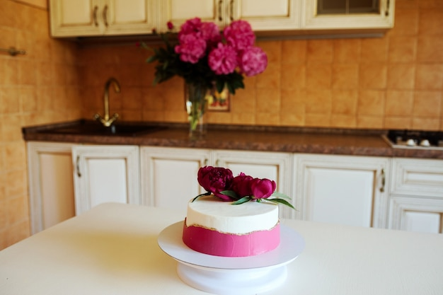 Un Beau Gâteau Décoré De Crème Rose Et De Pivoines Est Sur La Table De La Cuisine à L'intérieur. Photo Premium