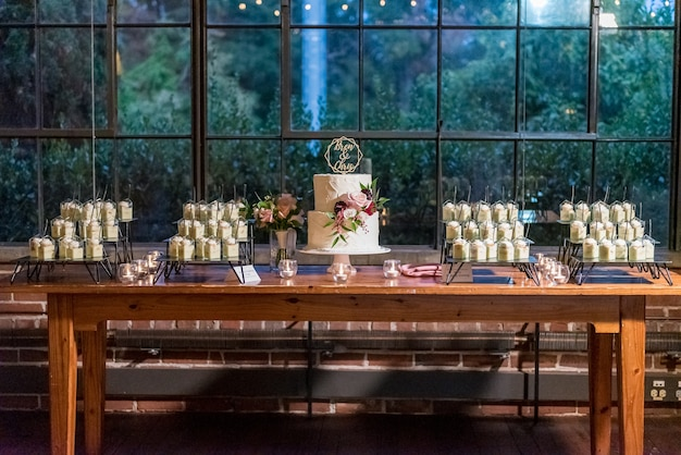 Beau Gâteau De Mariage Blanc Avec Différents Desserts Dans Des Tasses Sur Le Conte Photo gratuit