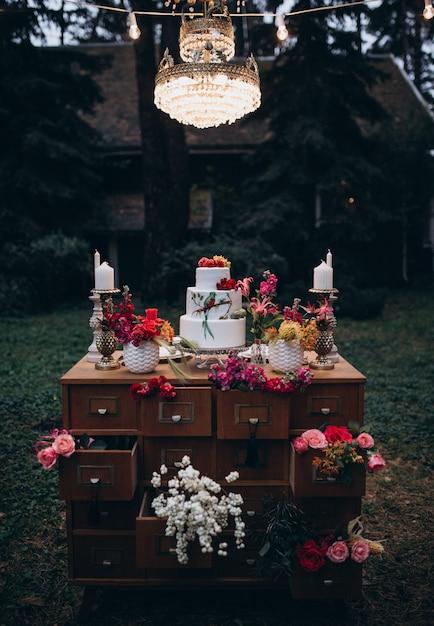 Un Beau Gâteau De Mariage à Trois Niveaux Décoré D'oiseaux, De Fleurs Roses Et De Branches Avec Des Feuilles Vertes Dans Un Style Rustique. Dessert Festif. Concept De Mariage. Photo Premium