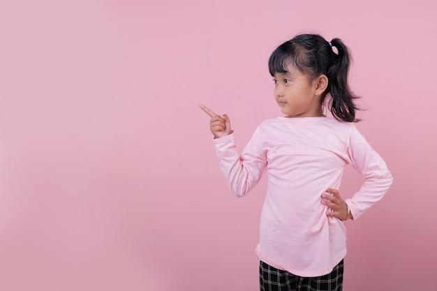 Un Beau Gosse Pointant Quelque Chose Portant Un T-shirt Rose Tendre Photo Premium
