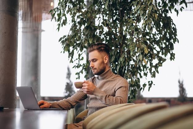 Beau homme d'affaires travaillant sur ordinateur et boire du café dans un café Photo gratuit