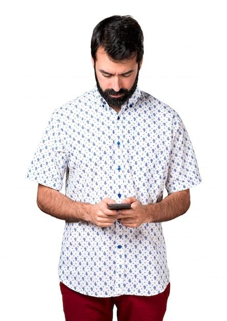 Beau homme brune à la barbe parlant au mobile Photo gratuit