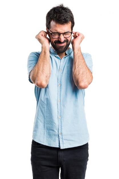Beau homme couvrant ses oreilles Photo gratuit