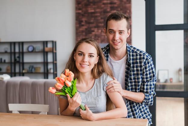 Beau homme étreignant femme avec de belles fleurs Photo gratuit