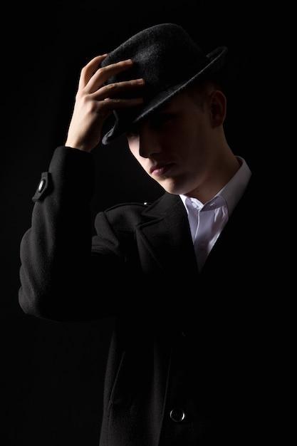 Beau homme mafieux touchant le chapeau dans le noir Photo gratuit
