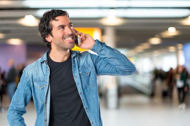 Beau homme parler à mobile sur fond blanc Photo gratuit