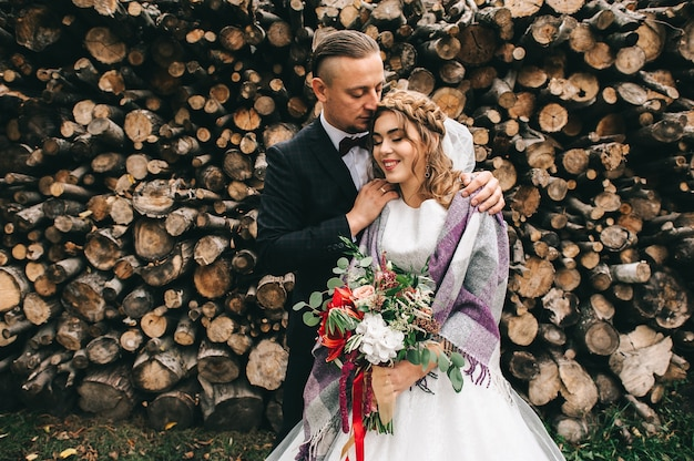 Beau jeune couple au jour du mariage sur le mur de fond avec des bûches en bois Photo Premium