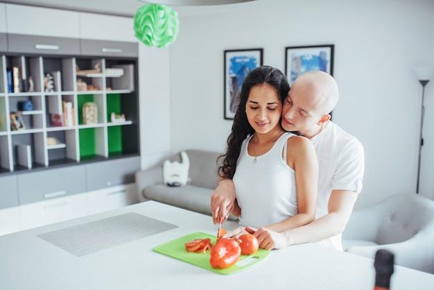 Beau Jeune Couple Broie Des Légumes Dans La Cuisine. Photo Premium